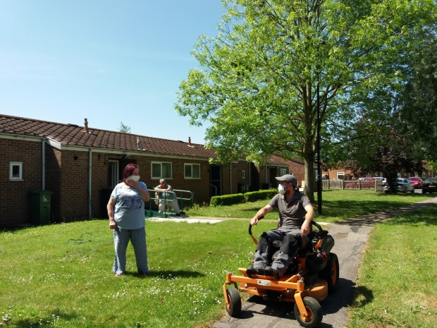 Staff member on lawn mower with residents in New Earswick