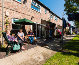 Residents sit in the sun outside homes in Clementhorpe Court, York
