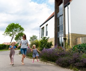 A family holding hands as they walk in Derwenthorpe