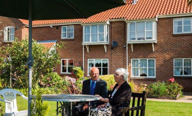 A man and woman sit in the gardens of Sandacre Court, in York