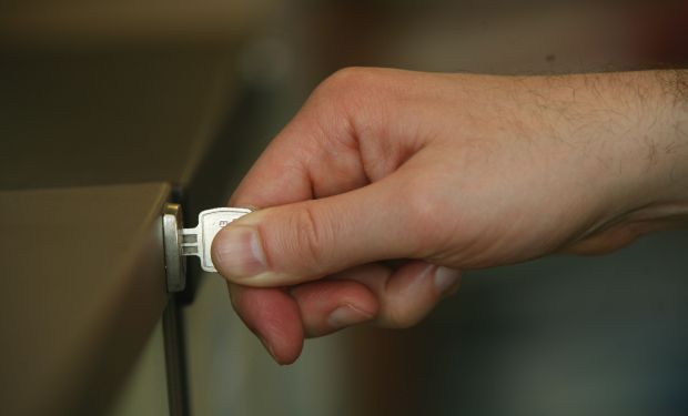 Hand turning key in filing cabinet